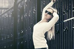 Blond fashion woman in sunglasses next to iron fence. In a city street Royalty Free Stock Photos