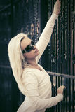Blond fashion woman in sunglasses next to iron fence Royalty Free Stock Photography