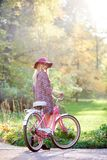 Blond fashionable long-haired attractive girl in short dress with lady bicycle in sunny park. Slim blond fashionable long-haired attractive girl in glasses stock photos