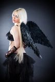 Blond female angel with black wings on a black background Stock Photography