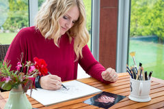 Blond female artist drawing from photography Stock Images