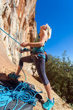 Blond Female Athlete belaying her Climbing Partner with Rope. Staying at orange rocky overhanging wall blue Sky Royalty Free Stock Photo