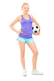 Blond female athlete holding a football. Full length portrait of a blond female athlete holding a football and listening music on headphones isolated on white Royalty Free Stock Image