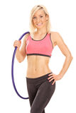 Blond female athlete holding a hula hoop. Isolated on white background Royalty Free Stock Images