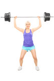 Blond female athlete lifting a heavy barbell. Full length portrait of a blond female athlete lifting a heavy barbell isolated on white background Stock Photo