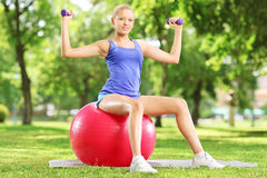 Blond female athlete in park sitting on ball and exercising with. Blond female athlete in park sitting on a pilates ball and exercising with dumbbells Royalty Free Stock Image