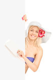 Blond female in bikini holding a travelling ticket and posing be Royalty Free Stock Photography