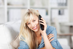 Blond female calling at home Royalty Free Stock Photo