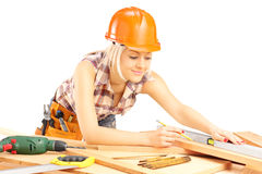 Blond female carpenter measuring a batten. Isolated on white background royalty free stock photos