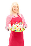 Blond female chef in apron holding a delicious cake stock photography