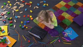 Blond female child watching cartoon on laptop, sitting on the floor at home. Stock footage stock video