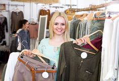 Blond female customer selecting new garments Royalty Free Stock Photos