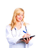 Blond female doctor making notes in papers Royalty Free Stock Image