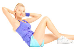 Blond female exercising abs on floor. Isolated on white background Royalty Free Stock Image
