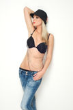 Blond female fashion model posing in black bra and jeans Royalty Free Stock Photography