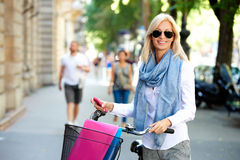 Blond female going to work by cycle Royalty Free Stock Photos