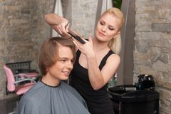 Blond female hairdresser cutting hair of man client. Stock Photo