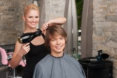Blond female hairdresser drying hair of man client. Royalty Free Stock Photo