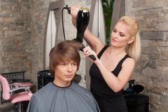 Blond female hairdresser drying hair of man client. Royalty Free Stock Photos