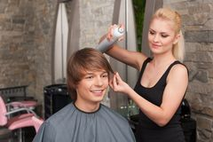 Blond female hairstylist using hair spray. Stock Images