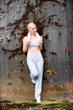 Blond female jogger leaning against a wall Stock Images