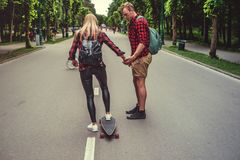 Blond female learnin ride longboard with casual male. Blond female in black leather pants practicing on longboard with her boyfriend Royalty Free Stock Images