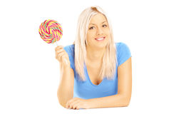 Blond female lying down with lollipop and looking at camera Royalty Free Stock Photo