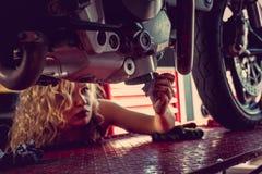 Blond woman repairing motorcycle. Blond female mechanic repairing motocycle engine. Close up image Stock Photography