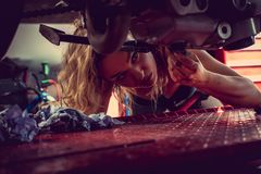 Blond woman repairing motorcycle. Blond female mechanic repairing motocycle engine. Close up image Royalty Free Stock Images