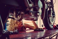 Blond woman repairing motorcycle. Blond female mechanic repairing motocycle engine. Close up image Royalty Free Stock Photos
