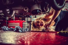 Blond woman repairing motorcycle. Blond female mechanic repairing motocycle engine. Close up image Royalty Free Stock Photo