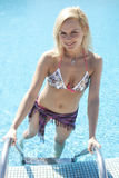Blond female model having fun in the pool Royalty Free Stock Images