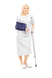 Blond female patient in gown with broken arm and crutch Royalty Free Stock Photography