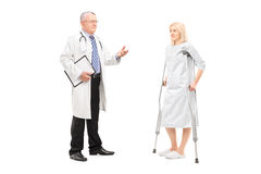 Blond female patient in hospital gown with crutches and medical. Full length portrait of a blond female patient in hospital gown with crutches and medical doctor Royalty Free Stock Photo