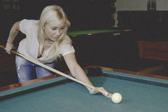 Female playing pool. Blond female playing pool in a poolhouse royalty free stock image