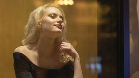 Blond female sitting at bar table alone, twisting hair on finger, attracting man. Stock footage stock video