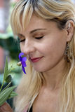Blond female smelling purple flower with her eyes clos Royalty Free Stock Images