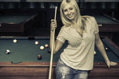 Female playing pool. Blond female standing in front of a pool table in a pool house stock photography