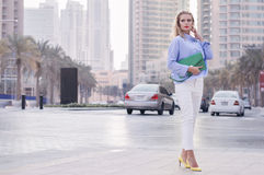 Blond female standing near busy road with cars in Dubai downtown Stock Images