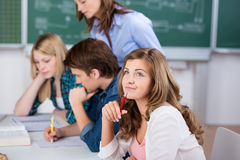 Blond Female Student With Classmates At Desk. Portrait of thinking blond female student with classmates at classroom desk Stock Image