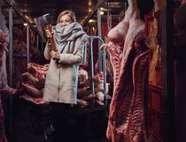 Blond female in a warm jacket in a meat freezer storage. stock photo