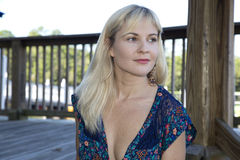 Blond female wearing a swimsuit cover up looking away from camera Royalty Free Stock Photo