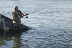 Blond fishing woman Stock Photo