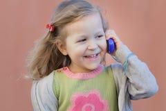 Blond flicka för förskolebarn som har gyckel under hennes dialog vid mobiltelefonen Fotografering för Bildbyråer