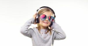 Blond flicka för härligt lyckligt roligt ungt barn med solglasögon som lyssnar till musik genom att använda hörlurar och att dans stock video