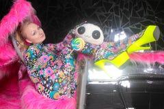 Blond flicka för klubbaparti i syrlig catsuit för animestilspandex med spegelbilen med rosa päls som är klar för galet klubba liv royaltyfri fotografi