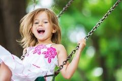 Blond flicka för litet barn som har gyckel på en gunga arkivfoton