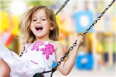 Blond flicka för litet barn som har gyckel på en gunga royaltyfri fotografi
