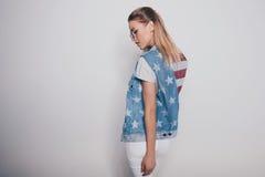 Blond flicka för stilfull hipster i amerikansk patriotisk dräkt och solglasögon som isoleras på grå färger Royaltyfri Foto