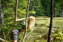 Blond flicka i en barrskog som ser sjön med näckrors Kanada royaltyfria foton